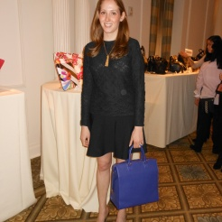 Katherine Saunders is wearing a Giorgio Armani outfit with Prada shoes and purple bag for a pop of color.